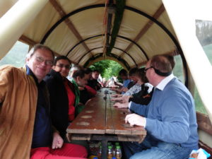 Im Planwagen_Foto von allen am Tisch_fotografiert von hinten am Einstieg