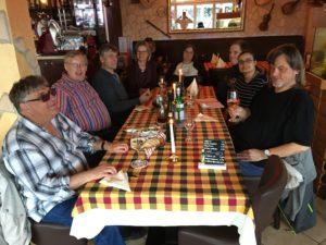 auf der linken Seite sitzen von vorne nach hinten Norbert, Ralf, Eberhard und Helene, an der schmalen Tischseite hinten sitzt Bianca und weiter auf der rechten Seite gegenüber von hinten nach vorne Jens, Anja und Rainer. Alle lächeln in die Kamera. Der Tisch ist mit einer rotkarierten Tischdecke eingedeckt auf der bereits Getränke, Oliven mit Brot und zwei Kerzenleuchter stehen.